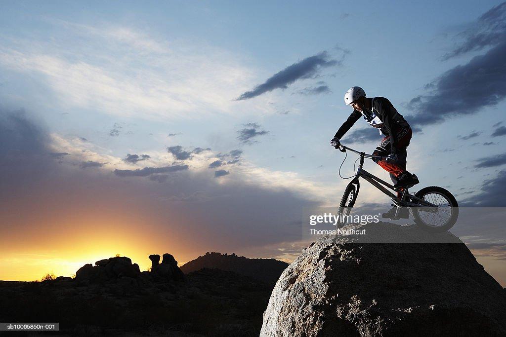 Bike rider balancing on rock boulder, side view : Stock Photo