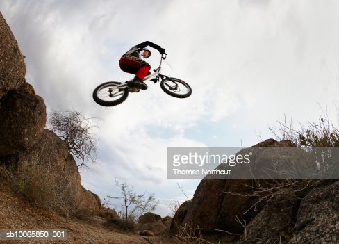 Bike rider jumping over gap between rocks low angle view for Jump the gap