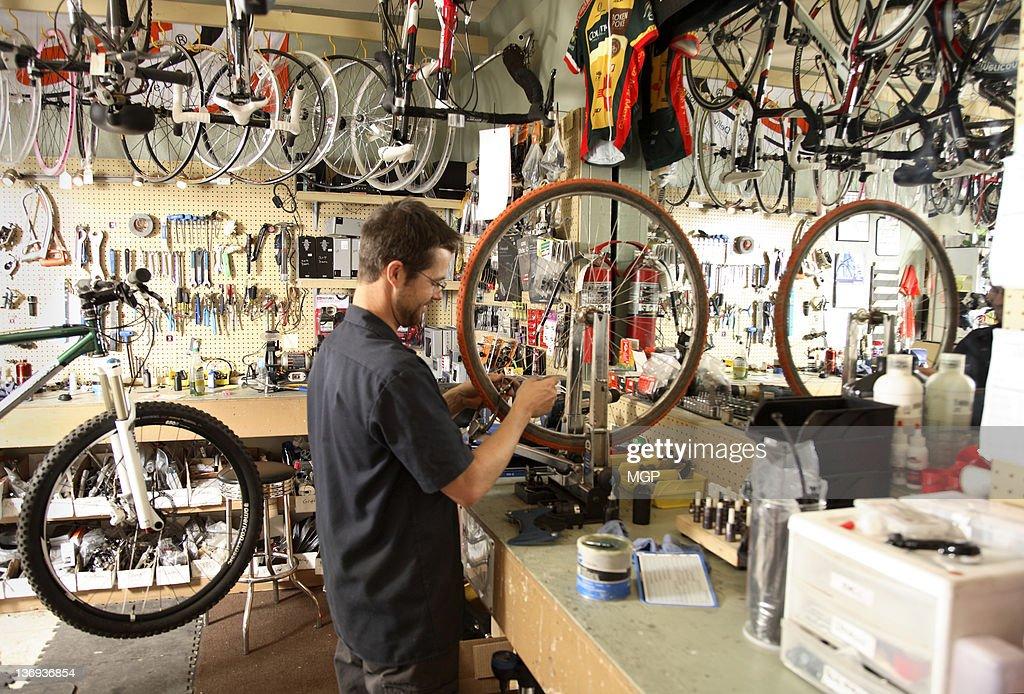 Bike shop owner fixes wheel : Stock Photo