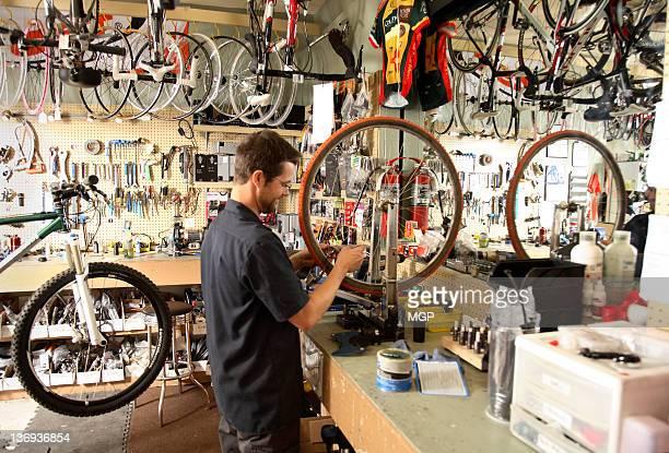 Bike shop owner fixes wheel