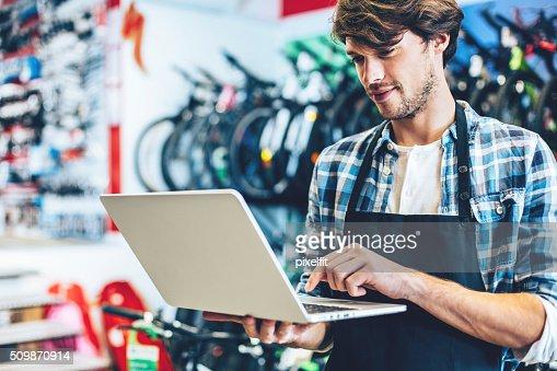 Bicicleta loja proprietário um trabalhar num um computador portátil