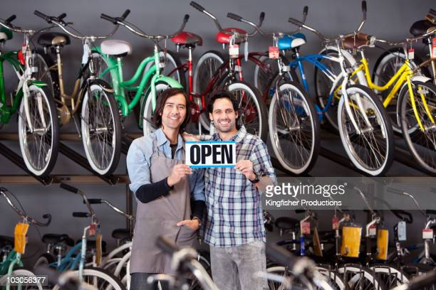Bike shop owners holding open sign