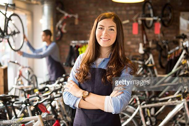 bike shop worker stands proudly in front of her stock