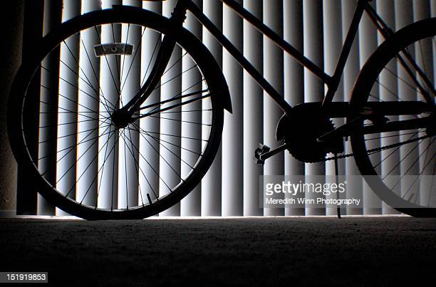 Bike spokes silhouetted against vertical lines