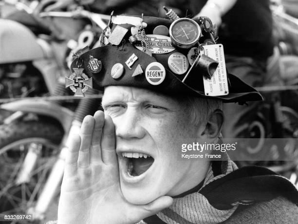 Biker avec un chapeau remplis de badges et médailles criant dans un rassemblement RoyaumeUni le 23 mai 1965