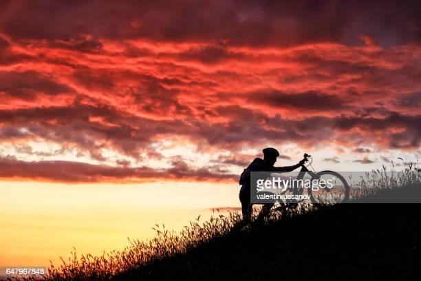 Biker, grimper sur la montagne au coucher du soleil