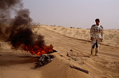 Biker De Boosere stands in front of what remains of his Honda motorbike in flames in the Gao desert during the 1990 Paris Dakar Rally