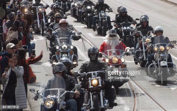 A biker dressed as Santa Claus drives along with around 1500 other Harley Davidson motorbike enthousiasts during a parade of the Prague Harley Days...