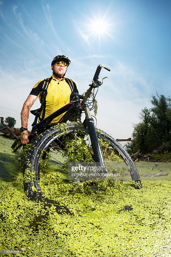 Biker getting out of water : Stock Photo