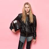 Biker girl wearing black leather jacket holding motorcycle helmet.