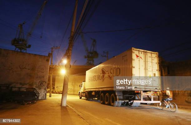 A biker hitches a ride along the back of a truck hauling a shipping container in front of a shuttered shipyard in the Caju neighbourhood which houses...