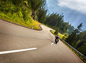 Biker in Austrian mountains riding on curve road, Alps, Europe, speed and freedom concept, luxury transport, active travel and tourism