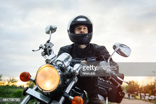 Biker in helmet driving motorcycle on sunset. : Stock Photo