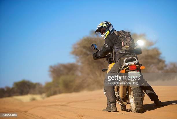 Biker looking over his shoulder, Central Kalahari Desert, Botswana