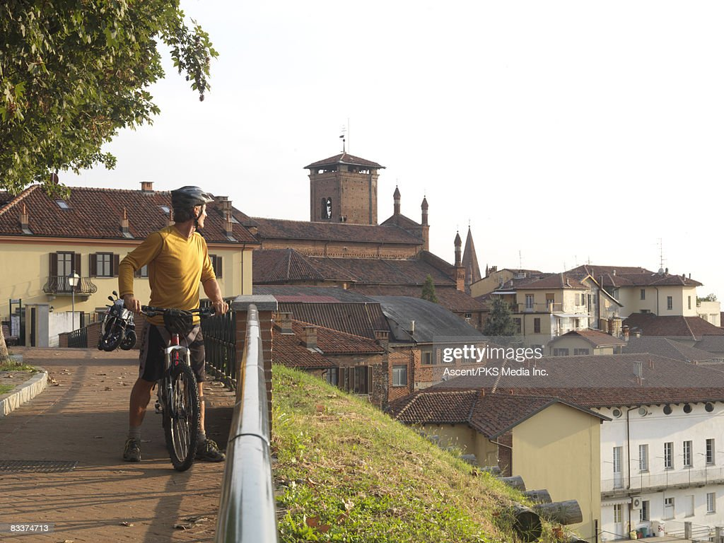 Biker looks over historic town centre from walkway : Stock Photo