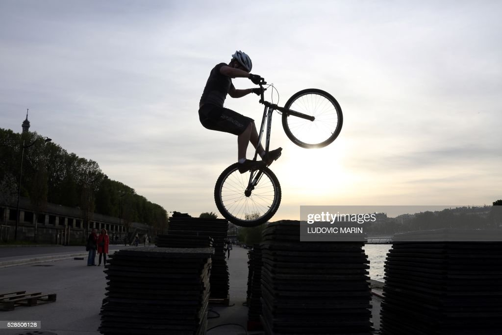 A biker practices his VTT-trial riding skills along obstacles stacked along the banks of the River Seine at sunset, in Paris, on May 5, 2016. / AFP / LUDOVIC