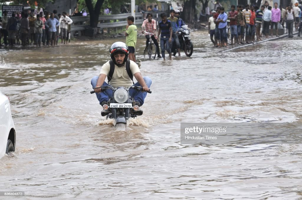 A biker raises his legs as he drives on waterlogged road of sector 44-50 dividing after the heavy rain on August 21, 2017 in Chandigarh, India. Heavy rainfall on morning brought the tri-city (Chandigarh, Mohali, Panchkula) to a stand still as poor drainage system gave way to roads being flooded with water. The rainfall left the cars of commuters stuck in middle of the roads forcing them to leave their cars stranded.