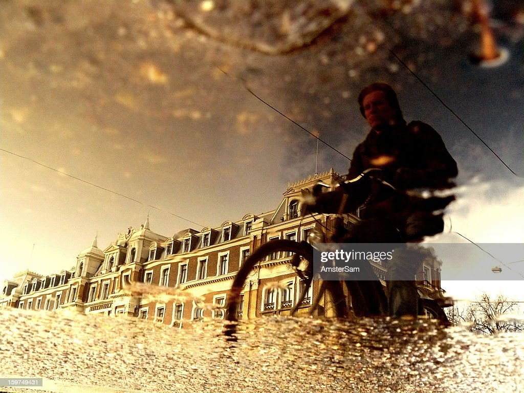 CONTENT] Biker reflected in a puddle in Amsterdam. Some contrast and saturation added, no Photoshop.