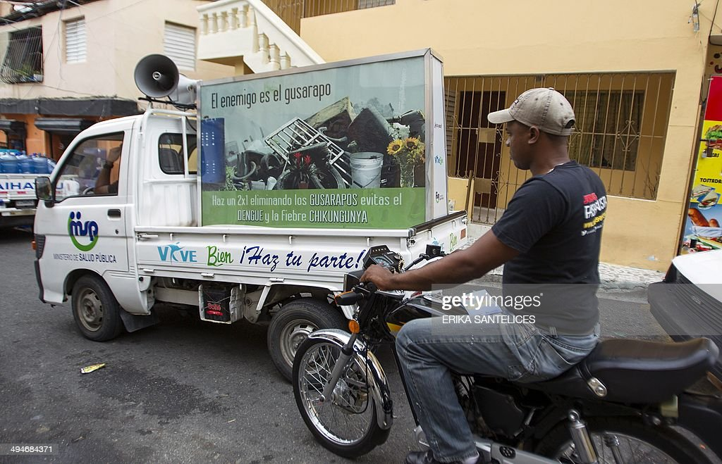 A biker rides next to a pick-up of the Dominican Ministry of Public Health displaying a billboard during an information campaign to prevent the spread of the mosquito which transmits the Chikungunya virus, in the district of 'La Agustinita', in Santo Domingo, on May 30, 2014. AFP PHOTO / ERIKA SANTELICES