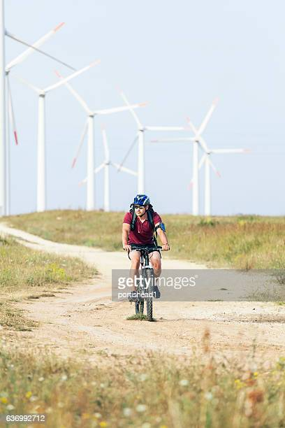 Biker riding in front of wind turbines