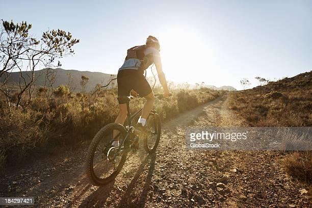 A biker riding on a gravel path at sunset
