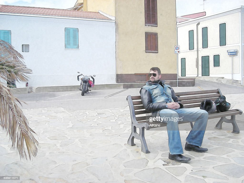 Motociclista sentado en un banco de : Foto de stock