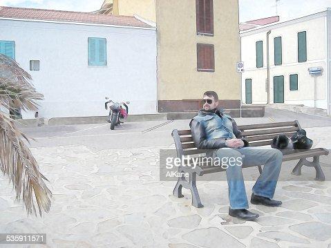 Motociclista sentado num banco : Foto de stock