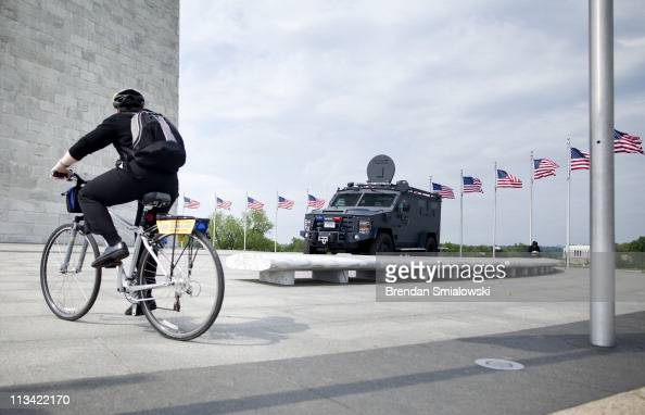 A biker stops as an armored Park Police vehicle sits parked at the base of the Washington Monument May 2 2011 in Washington DC The DC area and other...