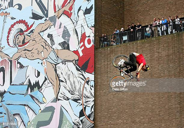 A biker taking part in the Tate Modern Urban Freeriding Mountain Biking Event jumps in front of New York artist Faile's work which is part of the new...