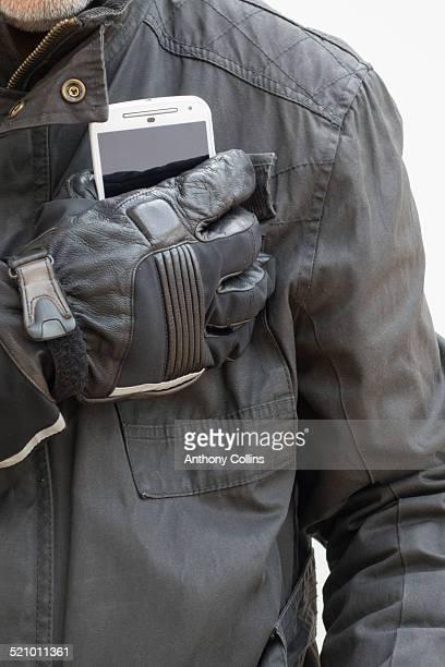 Biker taking smartphone from pocket of waxed cotton biker jacket