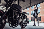 Handsome bearded biker with classic style black motorcycle. Cafe racer in garage.