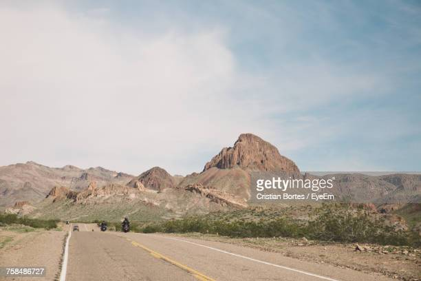 Bikers Riding Motorcycle On Route 66 Against Sky