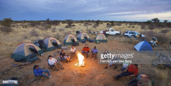 Bikers sit around a fire at camp, Central Kalahari Desert, Botswana