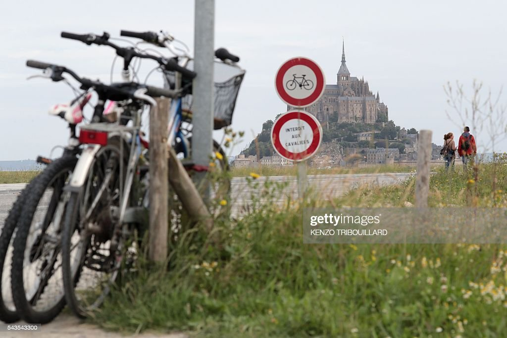 Bikes are parked ahead of a road sign indicating that cycling is prohibited beyond, in Le Mont-Saint-Michel, on June 29, 2016, three days before the start of the 103rd edition of the Tour de France cycling race. The 2016 Tour de France will start on July 2 in the streets of Le Mont-Saint-Michel and ends on July 24, 2016 down the Champs-Elysees in Paris. / AFP / KENZO