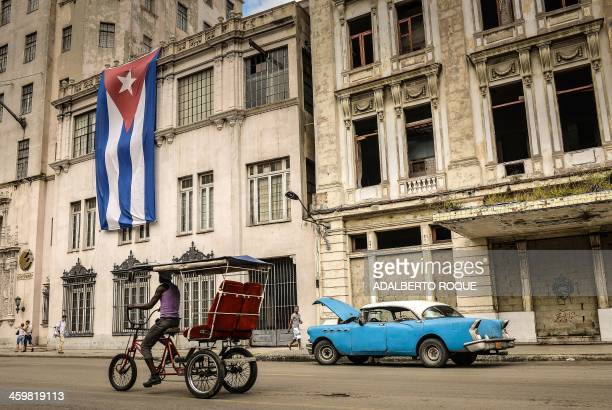 A biketaxi and a vintage American car are seen in front of a building decorated with a large Cuban flag on December 31 in Havana A new regulation...