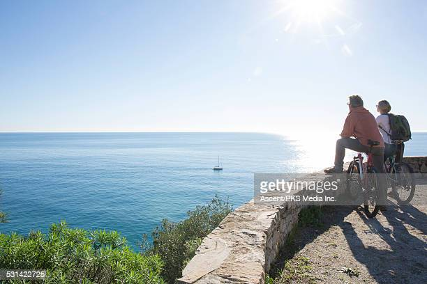 Biking couple look out to sea from rock wall perch