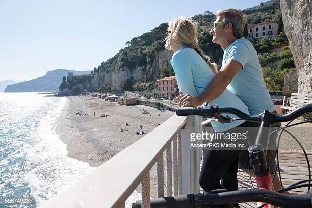 Biking couple relax with bikes above sea, beach