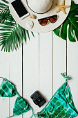 Bikini suit, hat, sunglasses, film camera, smartphone, sea star, green plam leaves arranged on wooden baclground. Summer holidays vacation concept. Vertical banner, postcard template.