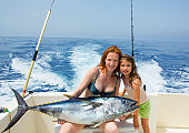 bikini fisher woman and daughter girl holding big bluefin tuna catch on boat deck