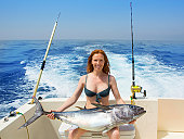 beautiful bikini fisher woman holding big bluefin tuna catch on boat deck