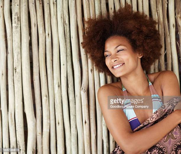 Bikini model smiles and leans against bamboo wall