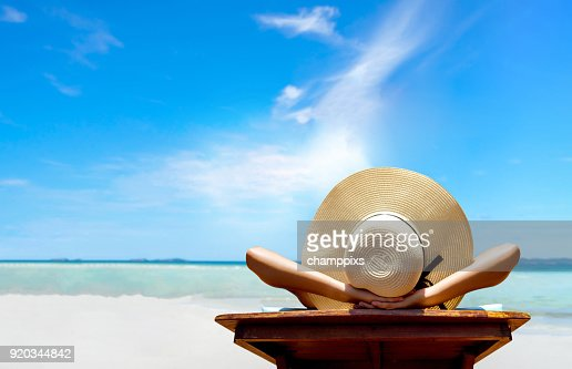 Bikini woman sexy in relax beach and resting resort in vacation on summer season with sunhat sitting chair sunbath with swimsuit alone at island lifestyle on weekend holidays : Stock Photo