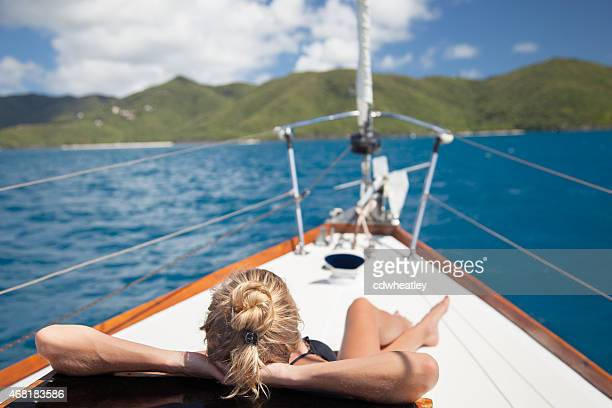 bikini woman sunbathing on a bow of  luxury sailboat