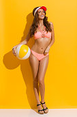 Smiling sexy woman with brown long curly hair, posing in sunlight in pink bikini, cork heels and red sun visor and holding beach ball under the arm. Full length studio shot on yellow background