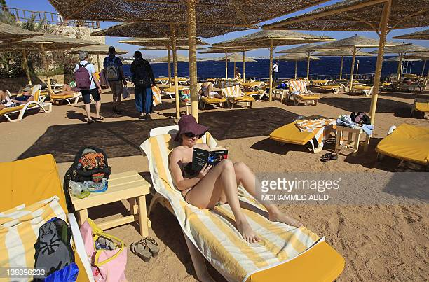 A bikiniclad tourist reads a book at the beach of the Red Sea resort town of Sharm elSheikh some 500 kilometers east of Cairo on January 3 2012 With...