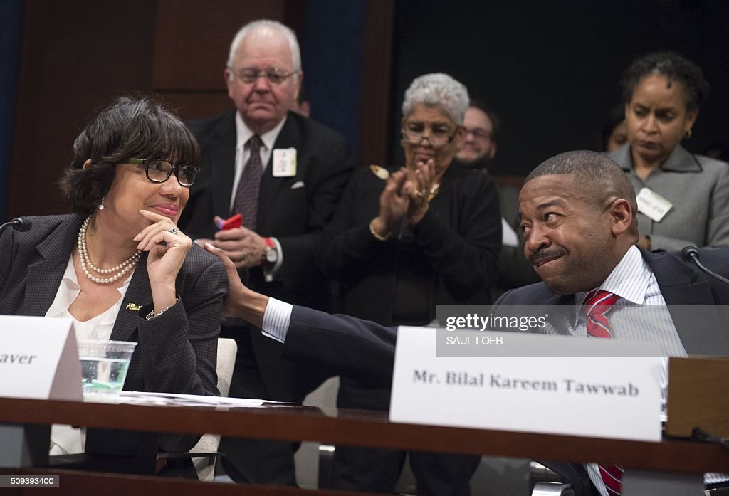 Bilal Kareem Tawwab, Superintendent of Flint, Michigan School District, places his hand on the shoulder of Mayor Karen Weaver (L) of Flint, Michigan, as she receives a standing ovation following her opening statement as she testifies about the lead levels found in Flint's water supply during a House Democratic Steering and Policy Committee hearing on Capitol Hill in Washington, DC, February 10, 2016. / AFP / SAUL LOEB