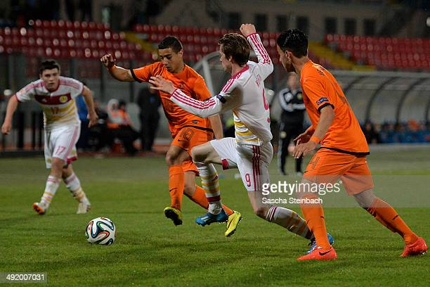 Bilal OuldChikh of Netherlands is challenged by Craig Wighton of Scotland during the UEFA Under17 European Championship 2014 semi final match between...