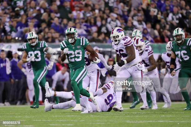 Bilal Powell of the New York Jets carries the ball as Ryan Davis of the Buffalo Bills defends during the third quarter of the game at MetLife Stadium...