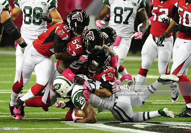 Bilal Powell of the New York Jets is tackled by Thomas DeCoud Stephen Nicholas and Desmond Trufant of the Atlanta Falcons at the Georgia Dome on...