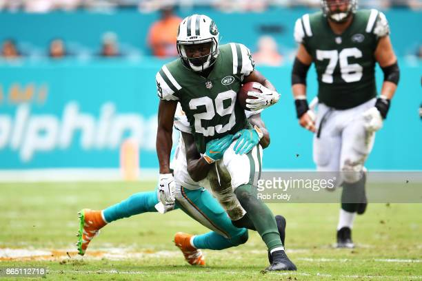 Bilal Powell of the New York Jets rushes against Reshad Jones of the Miami Dolphins during the second quarter at Hard Rock Stadium on October 22 2017...